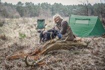 Dama sentada con perro disfrutando de desierto - foto de stock