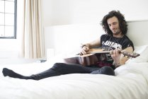 Man playing guitar in bed — Stock Photo