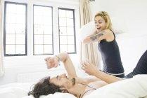 Tätowierte paar Kissen mit kämpfen auf Bett — Stockfoto