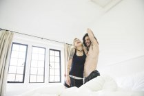 Tattooed couple having pillow fight on bed — Stock Photo