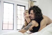 Tattooed couple cuddling on bed — Stock Photo