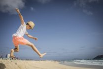Boy jumping in sand dunes at beach — Stock Photo