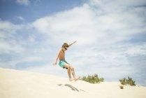 Garçon sautant dans les dunes de sable sur la plage — Photo de stock