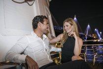 Couple enjoying drink on deck of boat — Stock Photo