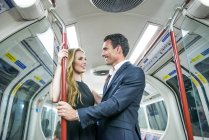 Coppia in piedi in treno del tubo — Foto stock