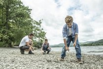 Man and boys skimming stones on shore — Stock Photo
