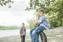 Boys playing on tyre hanging from tree — Stock Photo