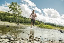 Man striding across shallow river — Stock Photo