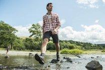 Uomo a passo di passo attraverso il fiume poco profondo — Foto stock