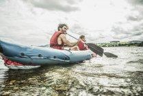 Homme et garçon en kayak pagaie de la rive — Photo de stock