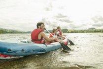 Homme et deux garçons en kayak pagaie. — Photo de stock