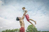 Homem brincando balançando menino no ar — Fotografia de Stock