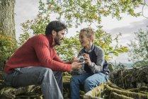 Мужчина показывает сыну, как пользоваться камерой — стоковое фото