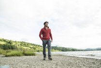 Man in red jumper standing on shore — Stock Photo