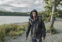 Человек в походных одежду, ходить на берегу — стоковое фото