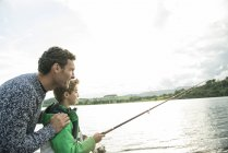 Father and son fishing from shore — Stock Photo