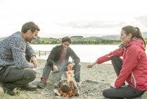 Three friends roasting marshmallows on shore — Stock Photo