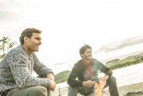 Amigos relaxantes em torno da fogueira na praia — Fotografia de Stock