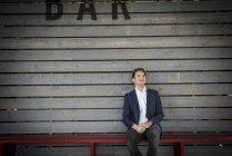 Man sitting on bench behind bar — Stock Photo