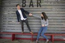 Paare, die Spaß hinter Bar — Stockfoto