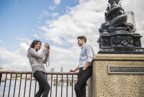 Donna scattare fotografie di giovane uomo — Foto stock