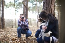 Man taking photo of girlfriend with dog — Stock Photo