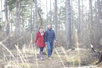 Couple walk with dog in woods — Stock Photo