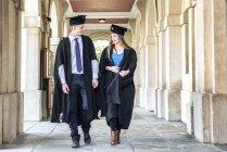 Studenten in Graduierung Kleider zu Fuß außerhalb Gebäude — Stockfoto