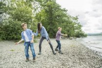 Woman and two boys playing on shore — Stock Photo