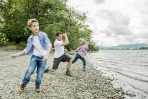 Man and two boys skimming stones — Stock Photo
