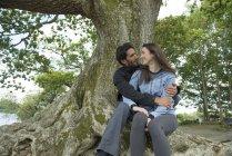 Двое влюбленных обнимаются на дереве — стоковое фото