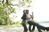 Man and woman playing on tyre hanging from tree — Stock Photo