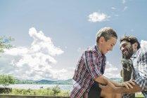 Man helping boy across stile — Stock Photo