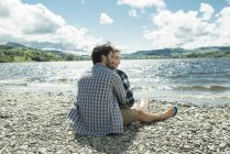 Man and woman sitting on shore — Stock Photo