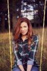 Woman in jeans on swing in winter garden — Stock Photo