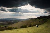 Pôr do sol vigas de luz em colinas no campo — Fotografia de Stock