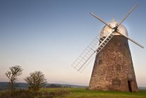 Moinho de vento ao pôr do sol no topo de colina — Fotografia de Stock