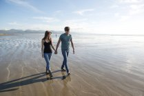 Couple walk holding hands across beach — Stock Photo
