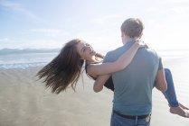 Man carrying partner across beach — Stock Photo