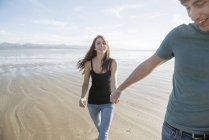 Пара ходьбы, взявшись за руки через пляж — стоковое фото