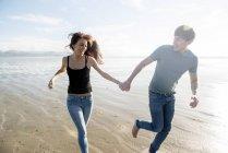 Пара работает удерживая руки на пляже — стоковое фото