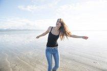 Woman enjoying sunshine on beach — Stock Photo