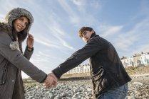 Paare, die Hände am Strand festhalten — Stockfoto