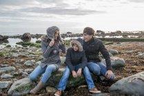 Пара і син, насолоджуючись, сидячи на скелі — стокове фото