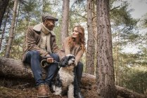Couple sitting on log with dog — Stock Photo