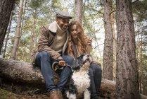 Paar, sitzen auf Log mit Hund — Stockfoto