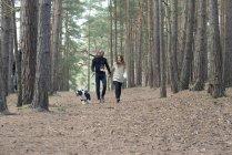 Coppia fuori con cane sulla passeggiata nella foresta — Foto stock