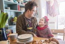 Pai senta-se na cozinha conversando com a filha — Fotografia de Stock