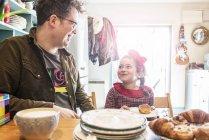 Père est assis dans la cuisine bavarder avec sa fille — Photo de stock