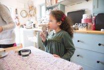 Mädchen steht am Küchentisch — Stockfoto
